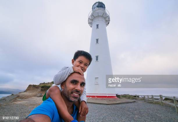 Father and son taking selfie with Castlepoint Lighthouse in background.