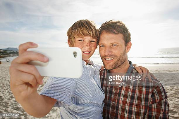 Father and son taking self-portrait, outdoors