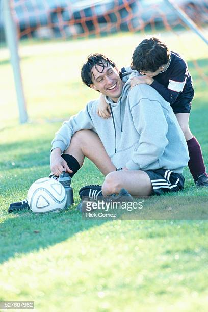 Father and Son Taking Soccer Break