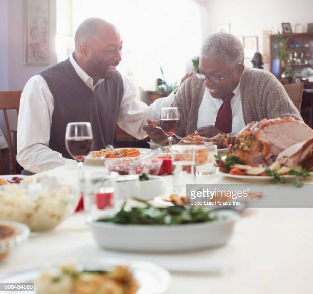 father and son talking at holiday table - african american family dinner stock photos and pictures