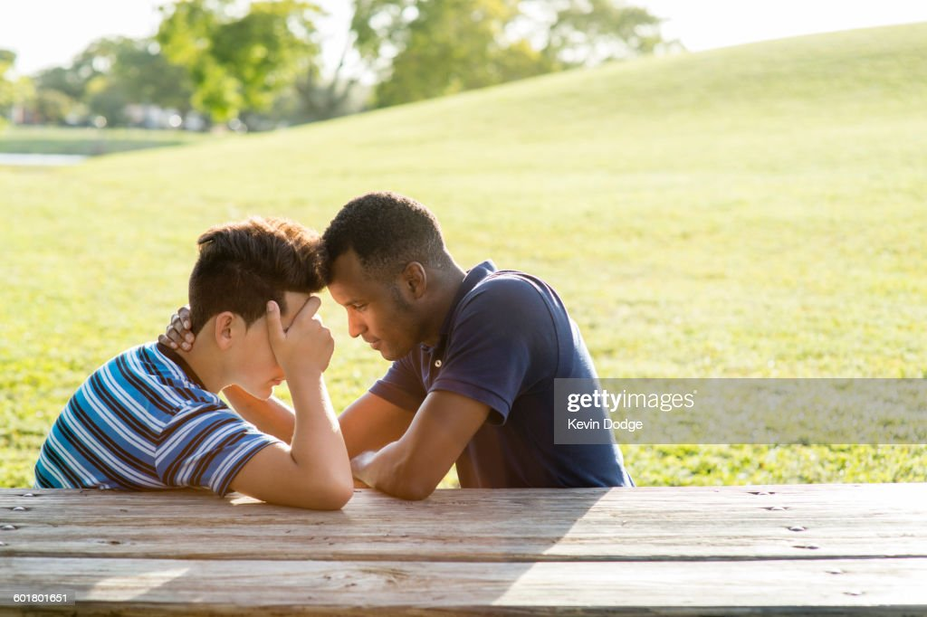 Father and son talking at table in park : Stock Photo