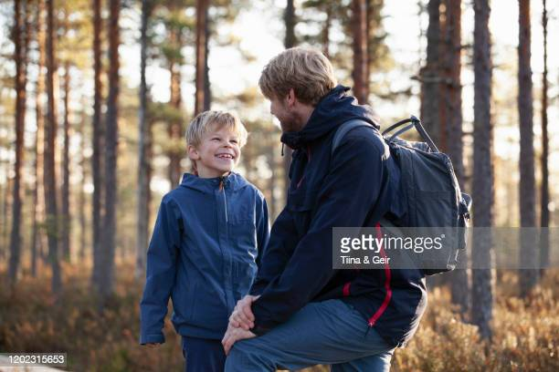 father and son talking in forest, finland - finland stock pictures, royalty-free photos & images