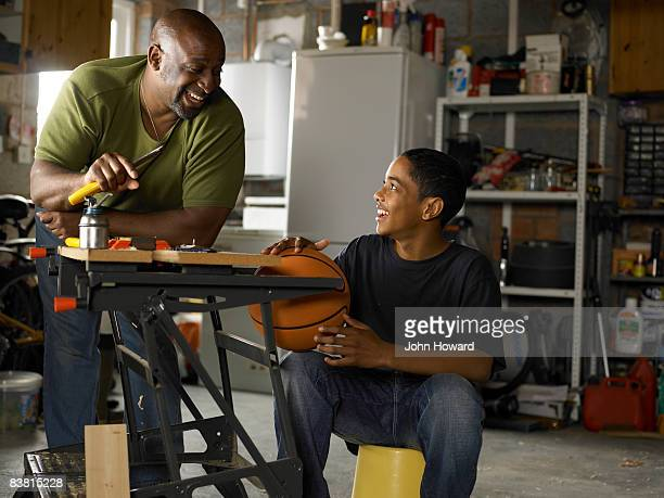 Father and Son talking over workbench in garage