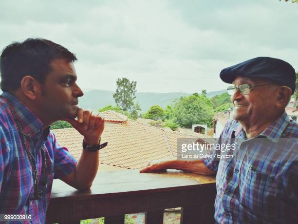 Father And Son Talking While Standing In Balcony Against Sky