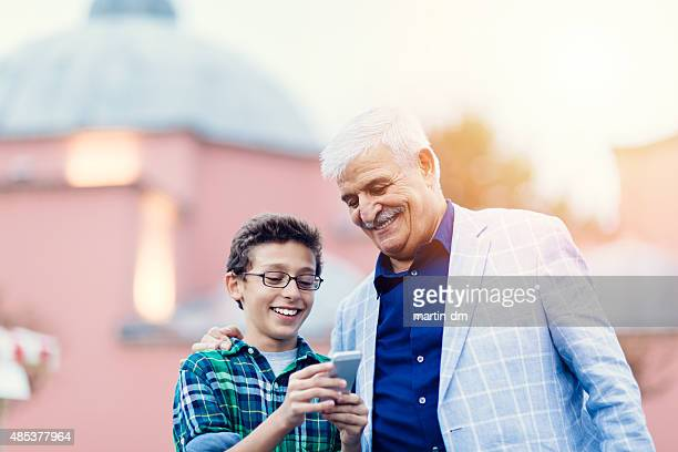 Father and son texting on smartphone outside