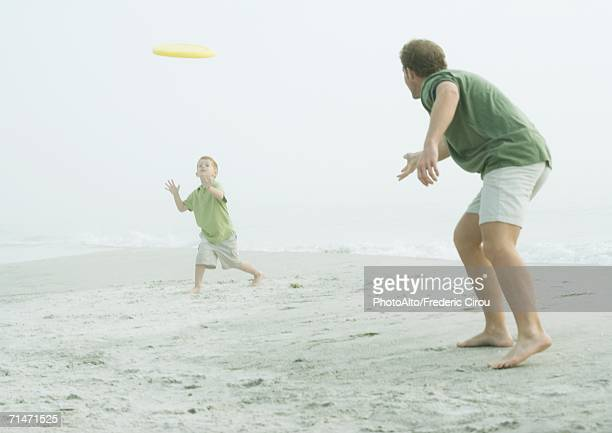 Father and son throwing flying disc on beach