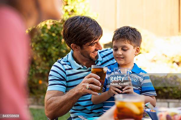father and son toasting in garden - rancho palos verdes stock pictures, royalty-free photos & images