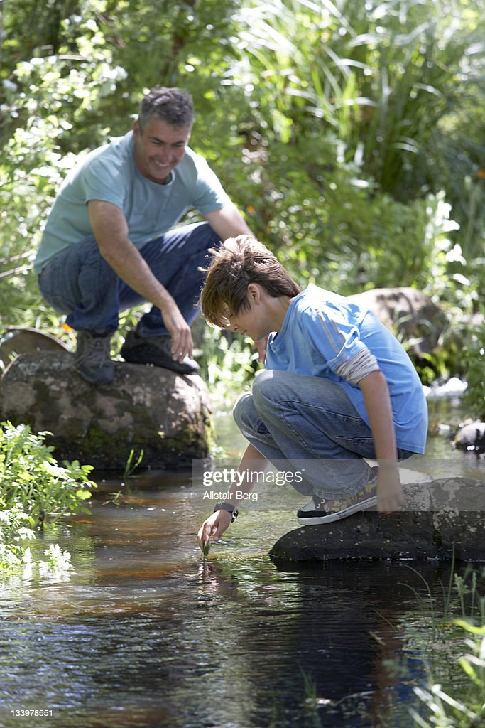 Father and son together by stream : Stock Photo