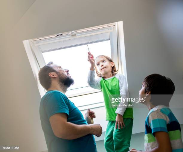 Father and son together checking roof window in smart house