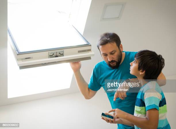 Father and son together controlling roof window in smart house