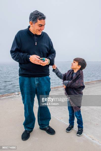 Father and Son Together next to large body of Water