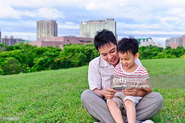 Father and son together using a smart phone