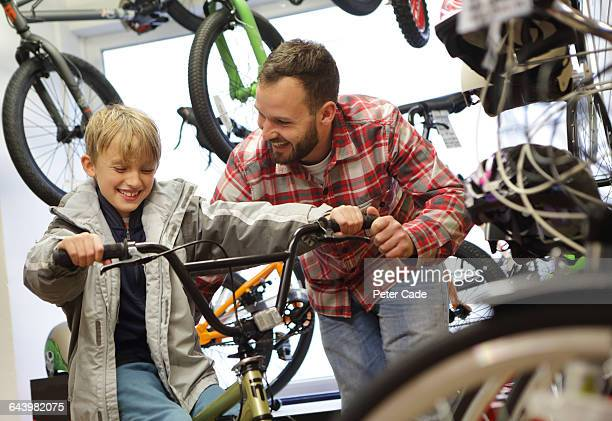 Father and son trying bike in shop