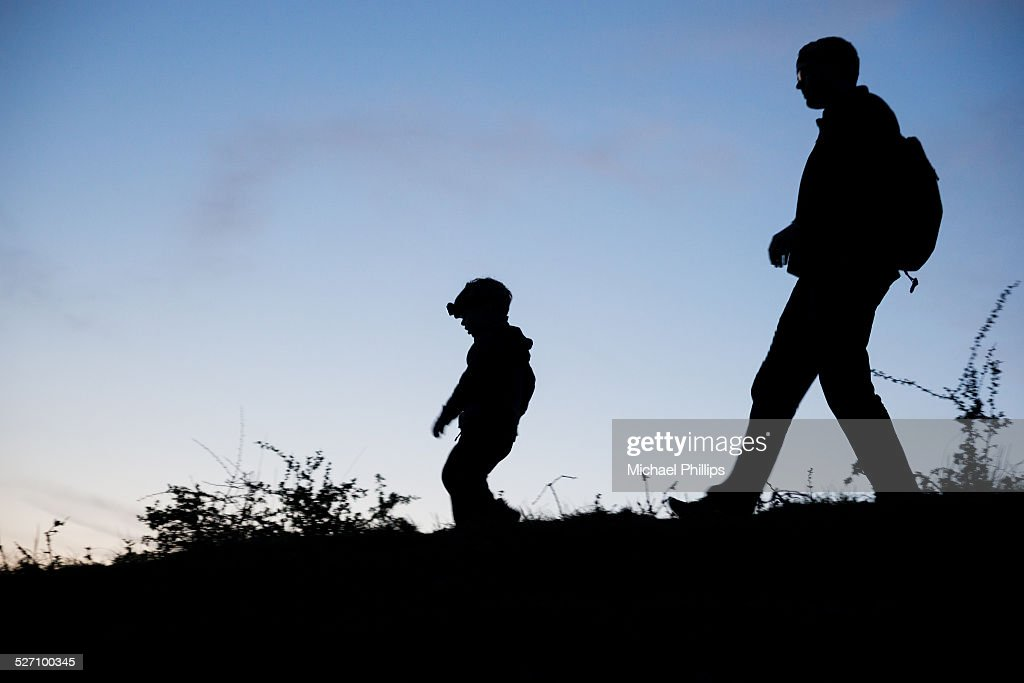 Father and Son Two walking figures silhouetted as they stroll along the horizon