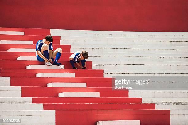 father and son tying shoes - uniforme de equipe - fotografias e filmes do acervo