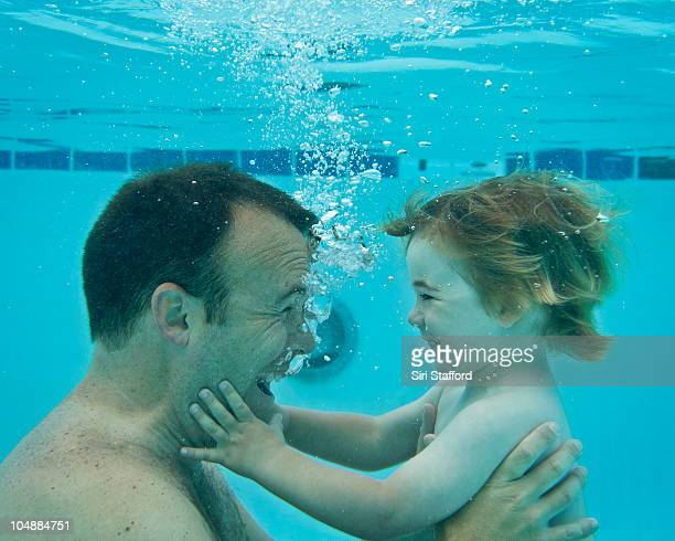 Father and son underwater looking at each other