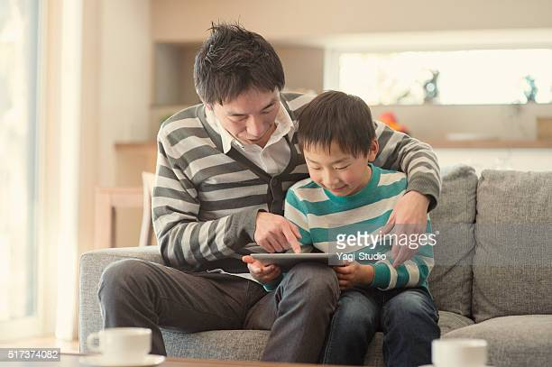 Father and son using a digital tablet on the sofa