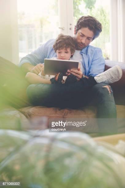 Vater und Sohn mit einem digitalen Tablet zusammen.