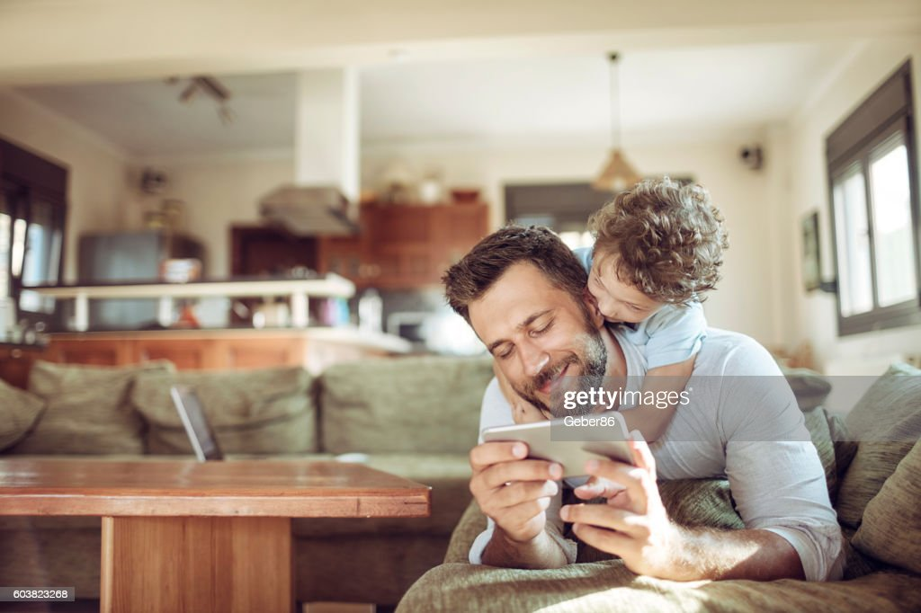 Father and son using a phone : Stock Photo