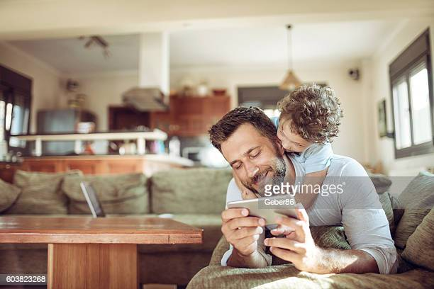 father and son using a phone - family home stock photos and pictures