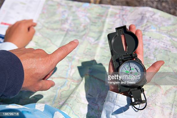 Father and son using compass and map