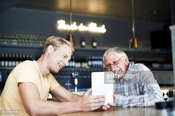 Father and son using digital tablet at cafe