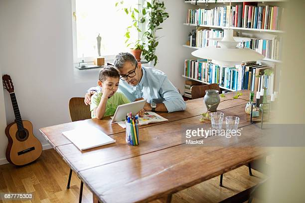 Father and son using digital tablet at table