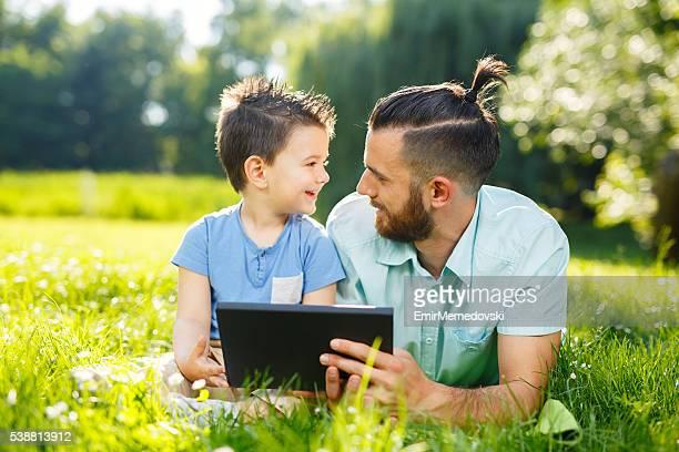 Vater und Sohn mit Digitaltablett in einem park.