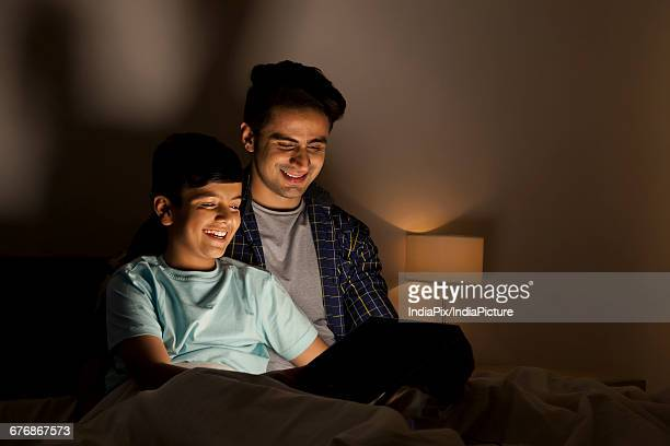 Father and son using digital tablet in bed at night