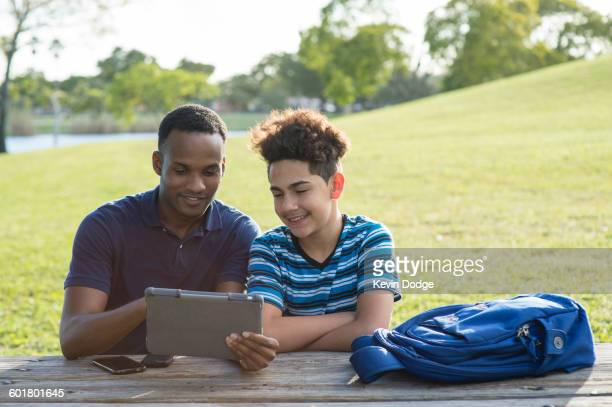 Father and son using digital tablet in park
