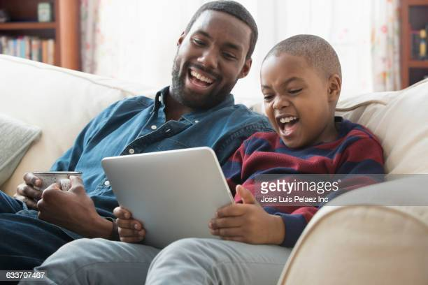 father and son using digital tablet on sofa - upload stock pictures, royalty-free photos & images