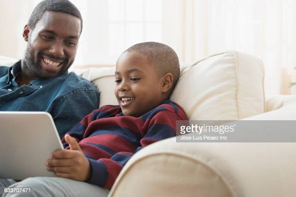 father and son using digital tablet on sofa - mood stream stock pictures, royalty-free photos & images