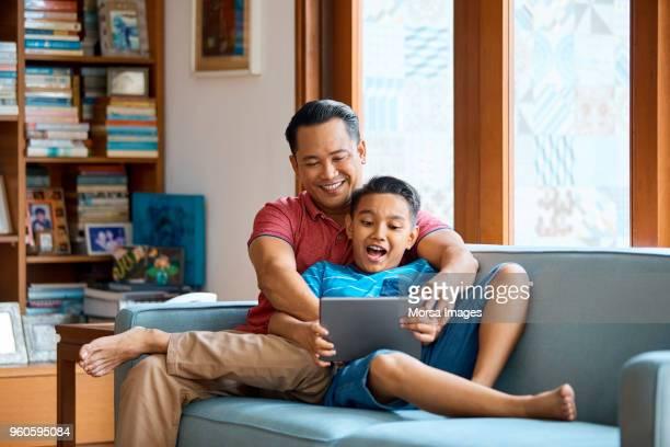 padre e hijo con tableta digital en sofá - malasia fotografías e imágenes de stock
