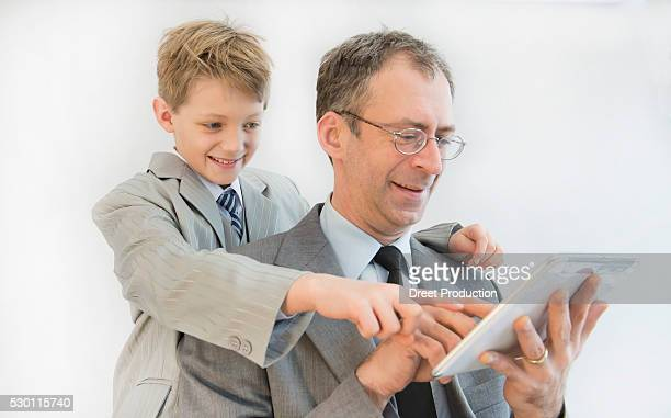 Father and son using digital tablet, smiling
