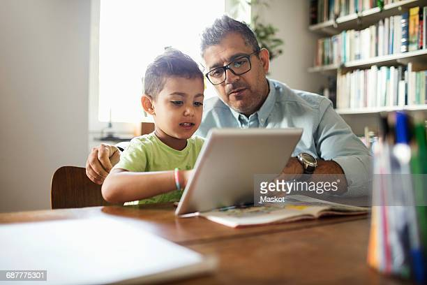 Father and son using digital tablet while studying at table