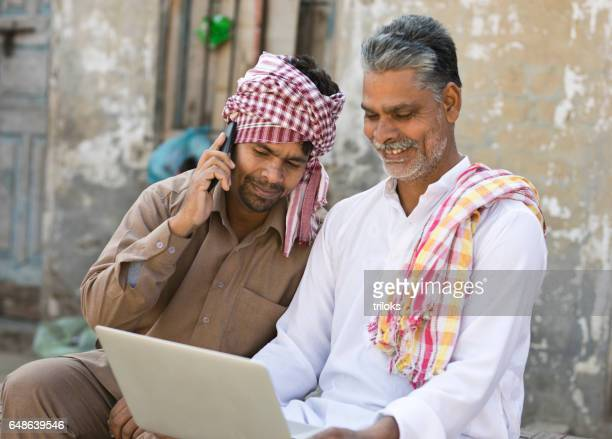 Father and son using laptop and mobile phone