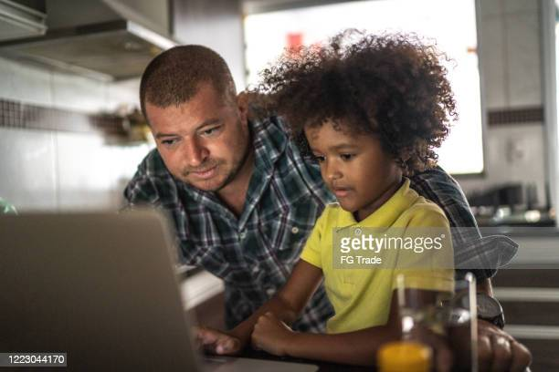 father and son using laptop at home - homeschool stock pictures, royalty-free photos & images