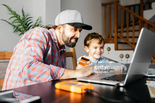 father and son using laptop together, online shopping - home shopping stock pictures, royalty-free photos & images