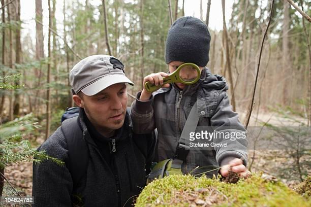 father and son using loupe - stefanie grewel stock-fotos und bilder