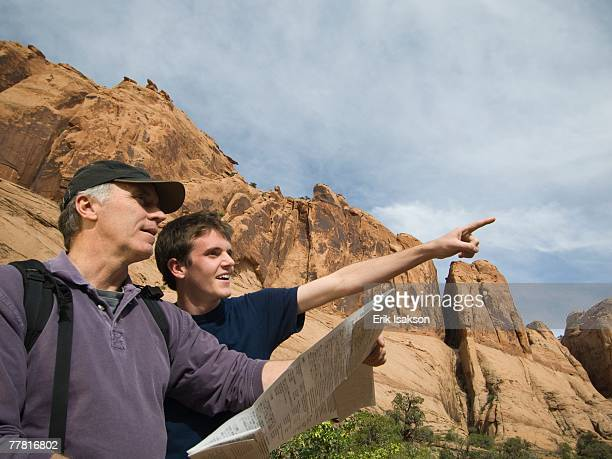 Father and son using map