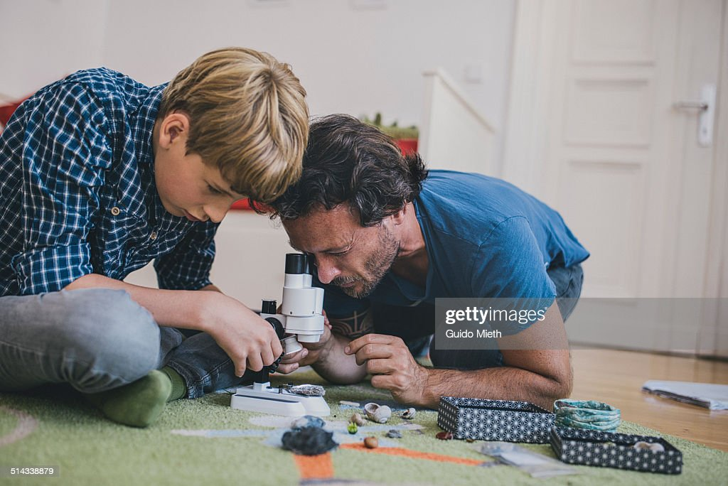 Father and son using microscope at home. : Stock Photo