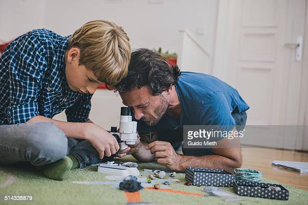 father and son using microscope at home. - uomini di età media foto e immagini stock