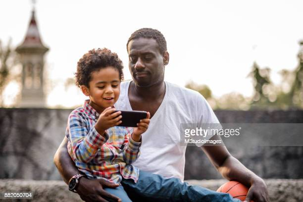 Father and son using mobile phone