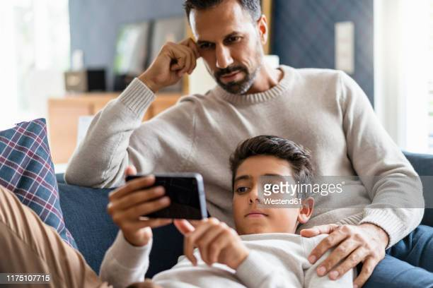 father and son using smartphone on couch in living room - männer über 30 stock-fotos und bilder