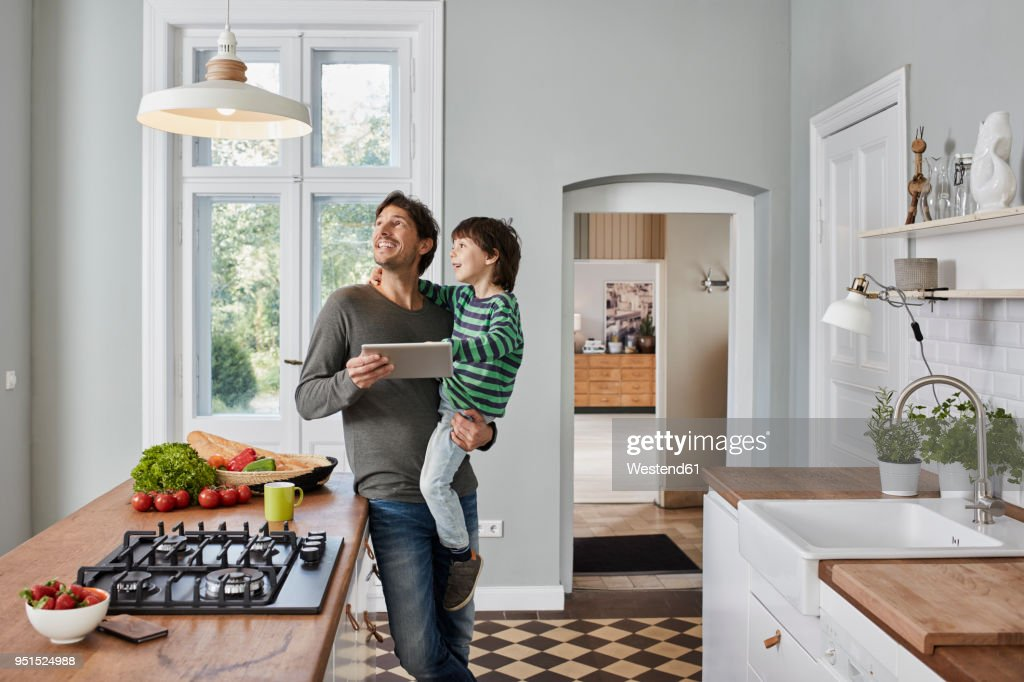 Father and son using tablet in kitchen looking at ceiling lamp : Stock Photo