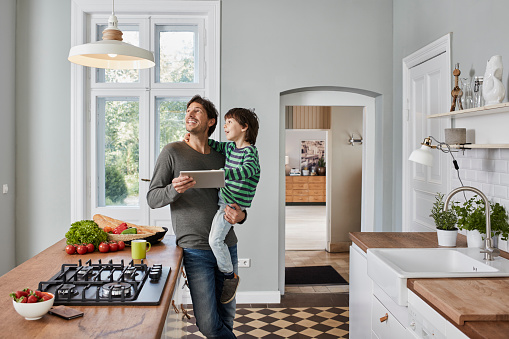 Father and son using tablet in kitchen looking at ceiling lamp - gettyimageskorea