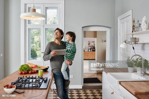 father and son using tablet in kitchen looking at ceiling lamp - huis stockfoto's en -beelden