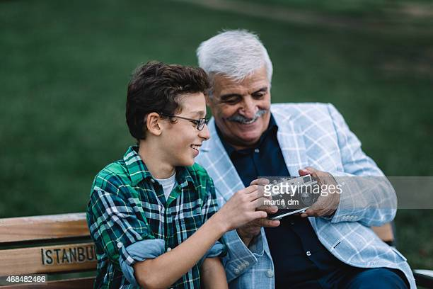Father and son using vintage camera in the park