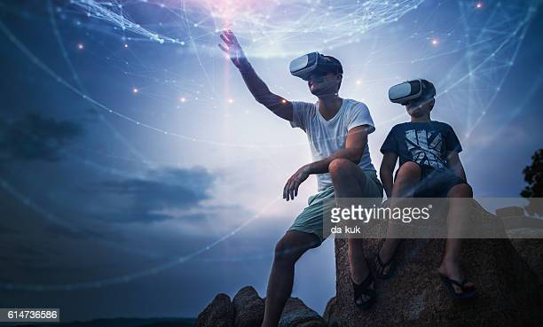 father and son using virtual reality glasses sitting outside - simulatore di realtà virtuale foto e immagini stock