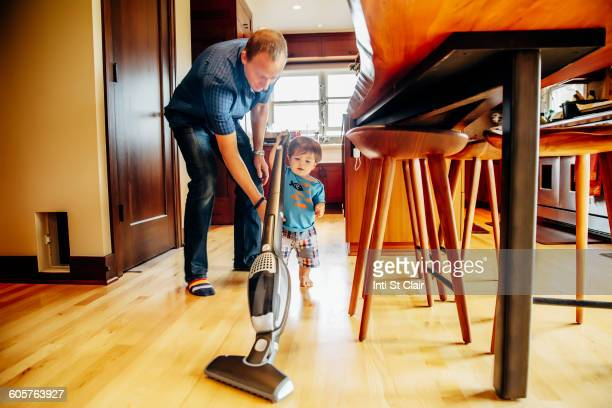 Father and son vacuuming kitchen